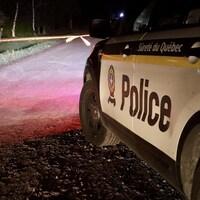 Une voiture de la Sûreté du Québec sur une route la nuit.