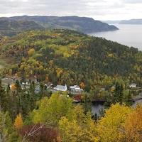 Un village se trouve en bordure de la rivière Saguenay.