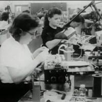 Femmes attablées, travaillant manuellement sur des produits électroniques.