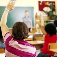 Des élèves lèvent la main dans une classe