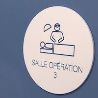 Une porte bleue avec une petite affiche sur laquelle on peut lire : salle opération 3 avec un icône