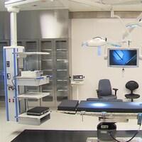 Une salle d'opération où l'on peut voir une table, des supports à instruments chirurgicaux et des écrans, notamment.