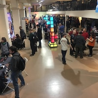 Des personnes s'attardent aux différents kiosques dans un salon de jeux vidéo et de jeux d'arcade.