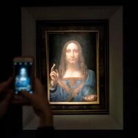 Un visiteur prend le tableau Salvator Mundi en photo.