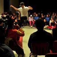 Un adolescent danse sous le regard attentif du public rassemblé autour de la piste.