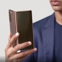 Un homme en complet tient le téléphone pliable Galaxy Z Fold 2 de Samsung.