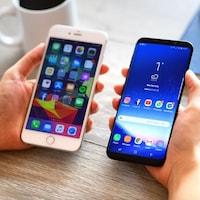 Une personne tient un iPhone 6 Plus à côté d'un Samsung Galaxy S9 Plus.