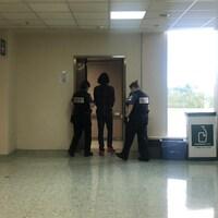 Samuel Cyr, de dos, entre dans un ascenseur. Il est menotté et est escorté par deux policiers.