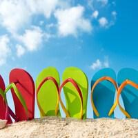 Des sandales apparaissent au sommet d'un petit monticule de sable.