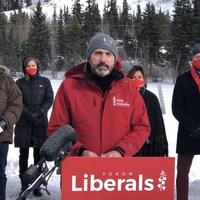 Sandy Silver parle au micro derrière une bannière du Parti libéral du Yukon.