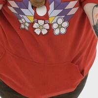 Une femme montre ses deux tatouages en forme de papillon qu'elle a sur les avant-bras.