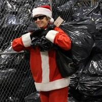 Une femme déguisée en mère Noël transporte un gros sac de vidanges.