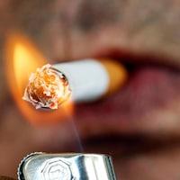 Un homme s'allume une cigarette avec un briquet.