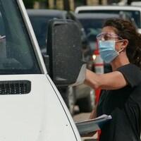 Une femme portant un masque debout qui parle à une personne assise dans une voiture.