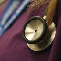 Un stéthoscope sur la poitrine d'une femme qui porte un uniforme.