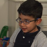 Santiago sourit à l'intervieweur, avec des jouets à l'arrière-plan.