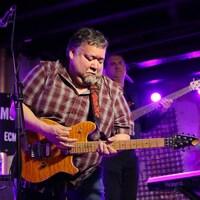 Gary Sappier joue de la guitare sur scène