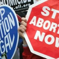 Un panneau bleu indiquant «Gardez l'avortement légal» et l'autre, rouge, disant «Arrêtez les avortements maintenant»