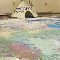 Une carte géorgraphique sur le sol, avec un tipi en fond d'image.