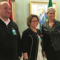 Trois personnes souriantes prennent la pause pour une photo dans le palais législatif de la Saskatchewan.