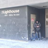 Deux hommes attendent à l'extérieur de l'immeuble du Lighthouse de Saskatoon.