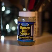 Un pot de sauce avec une étiquette bleue sur un comptoir.