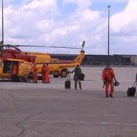 Des secouristes marchent sur un tarmac où se trouve un hélicoptère jaune.