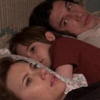 Une femme sur un lit regarde au plafond. Un enfant et un homme sont couchés à coté d'elle et la regardent.