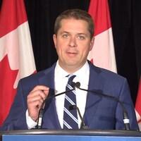Andrew Scheer, la main levée, regarde la caméra lors d'une conférence de presse.