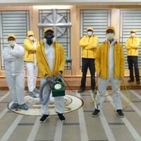 Un groupe de ministres volontaires avec des masques et des manteaux jaunes.