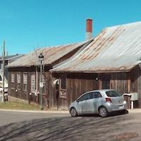 La scierie est faite de vieux bois, avec un toît en tôle. Une rue la longe.