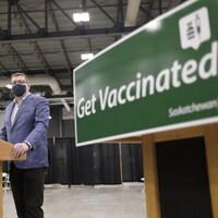 Scott Moe, devant un micro, près d'une pancarte «Get Vaccinated».