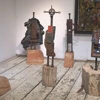 Des sculptures faites de retailles de métal sont exposées dans une salle de musée.