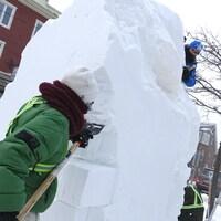 Des artistes sculptent un bloc de neige.