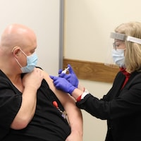 Une infirmière administre un vaccin à un homme.