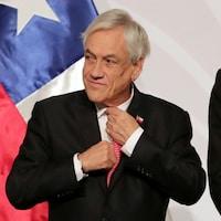 Sebastian Piñera ajuste sa cravate avant la prise d'une photo officielle lors d'une conférence internationale.