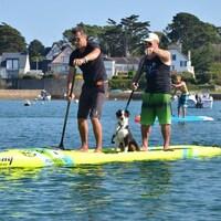 Deux hommes et un chien debout sur une planche à rames jaune.