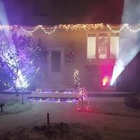 Des faisceaux de lumière sont projetés depuis la façade d'une maison décorée pour les Fêtes.