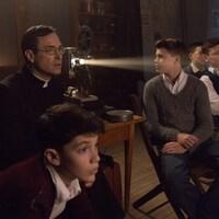 Un homme et quatre jeunes garçons regardent une projection de film dans une classe.