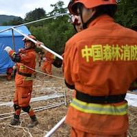 Des secouristes montent une tente.