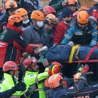 Des secouristes transportent un survivant sur une civière.