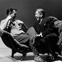 Dans un studio de télévision, l'écrivain américain Jack Kerouac et l'animateur Fernand Seguin, riant, sont assis sur une causeuse.