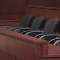 On aperçoit un box de jurés vide dans un tribunal.