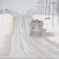 Une saleuse sur une route en hiver.