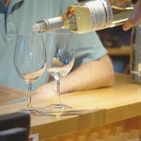Un vin blanc du vignoble St Hubertus est versé dans un verre à vin.
