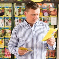 Un homme choisit des semences dans un magasin.
