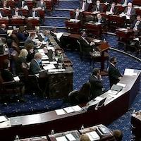 Des élus américains, certains portant des masques, siègent au Sénat.
