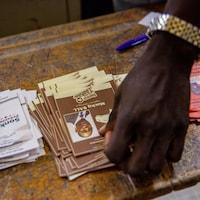 Une main est posée sur un paquet de pamphlets des différents candidats à l'élection présidentielle déposés sur une table en bois.