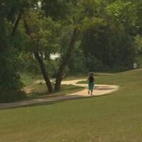 Une femme, de dos, court sur un sentier dans un environnement entouré de gazon et d'arbres.