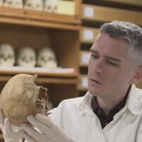 Gros plan d'un chercheur regardant un crâne.